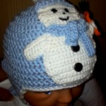 Cappellino di lana con paraorecchie e pupazzo di neve